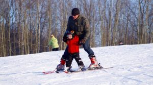 gemeinsames Skifahren von Kind und Mann